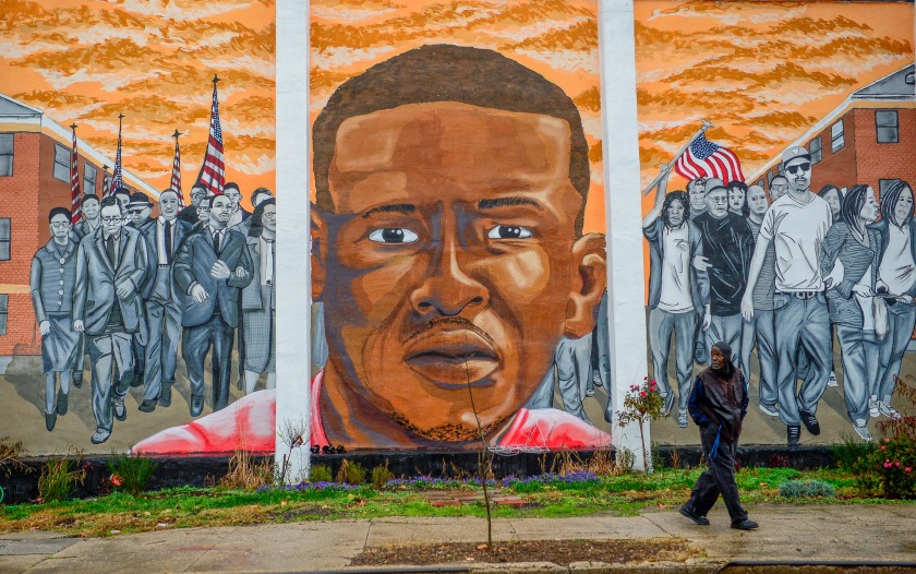 A man walks past a mural of Freddie Gray in the Sandtown-Winchester neighborhood of Baltimore
